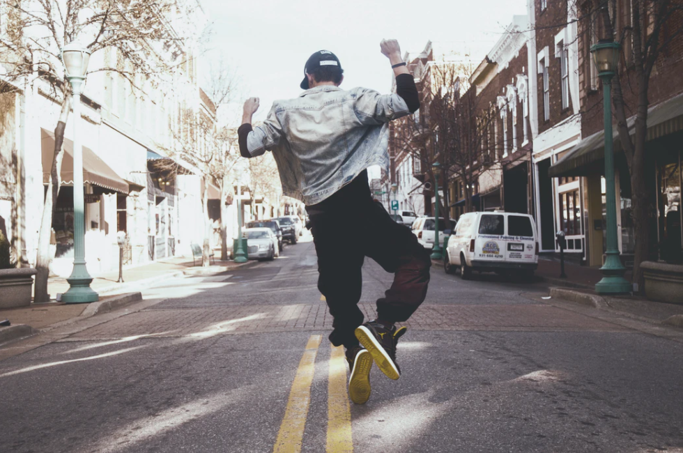 A man jumping while listening to happy mp3 background music for videos